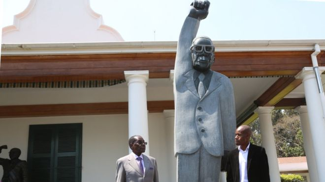 Dominic Benhura stands next to his 'masterpiece' besides a polka faced President Robert Mugabe